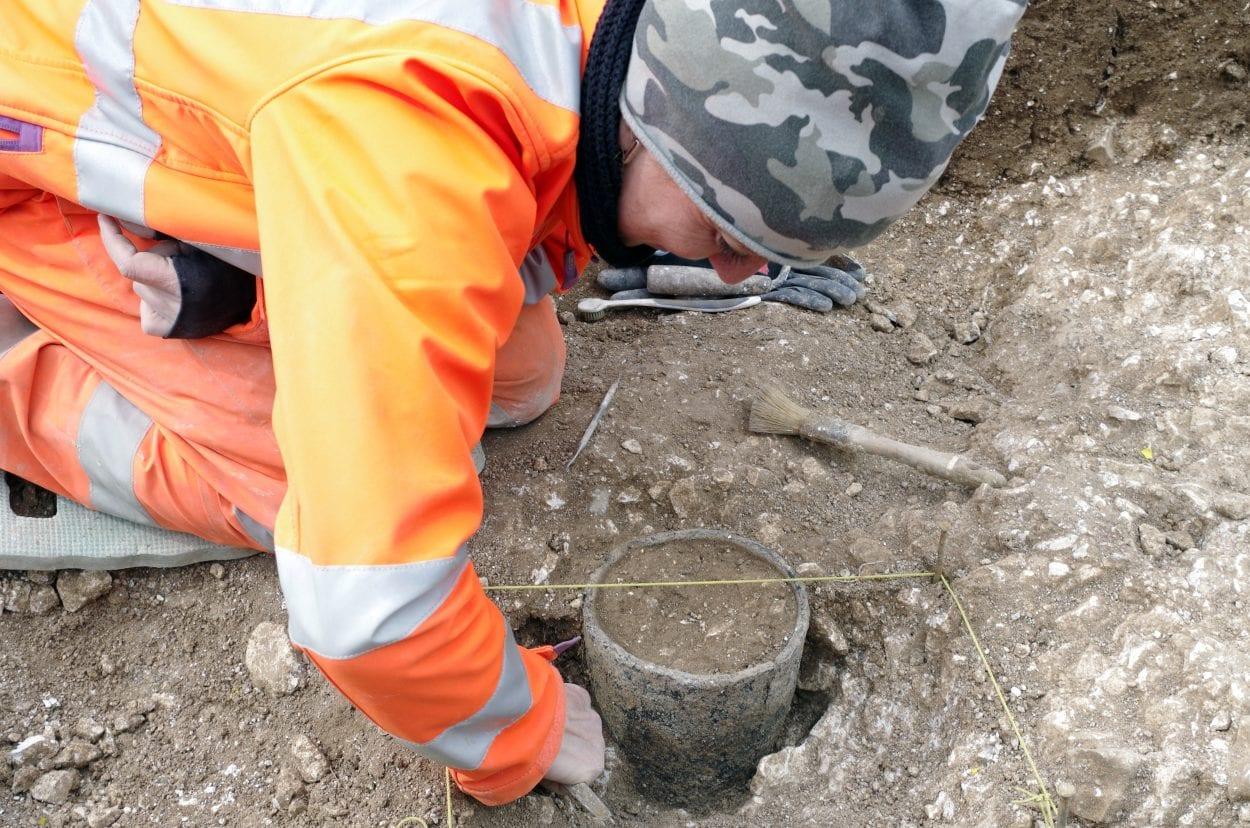Archeolog s archeologem Wessex vykopává nádobu z doby bronzové objevenou během přípravných prací na místě navrhovaného tunelu poblíž Stonehenge. (Obrazový kredit: Wessex Archaeology)