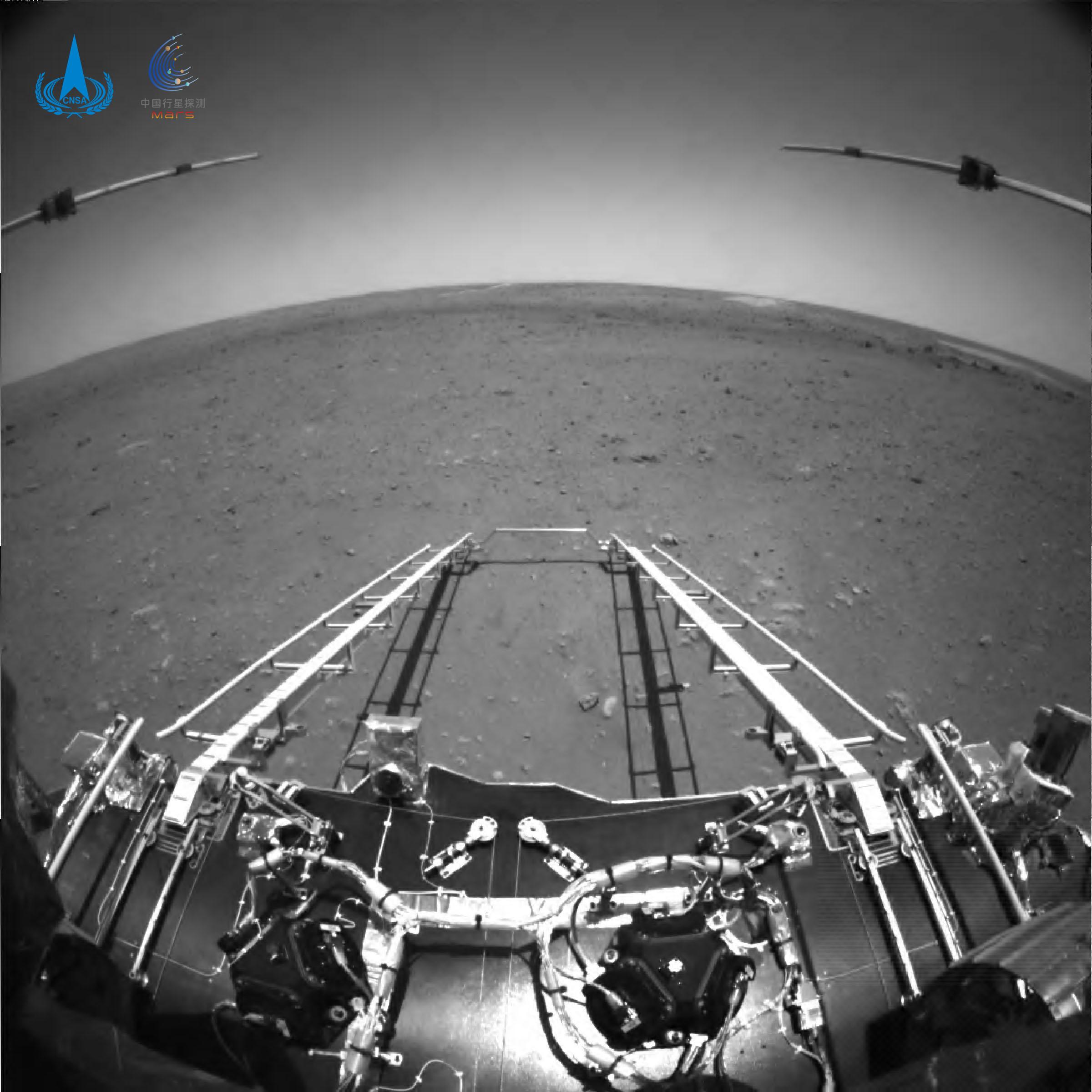 Tento černobílý pohled na Mars je fotografie z navigační kamery na čínském marsovském vozidle Zhurong zveřejněná 19. května 2021 asi 4 dny po přistání. Je vidět rampa na marťanský povrch z Zhurongova přistávacího modulu, stejně jako dva podpovrchové radarové přístroje na roveru a marťanský horizont v širokoúhlém pohledu. (Credit: Čínský národní vesmírný úřad)